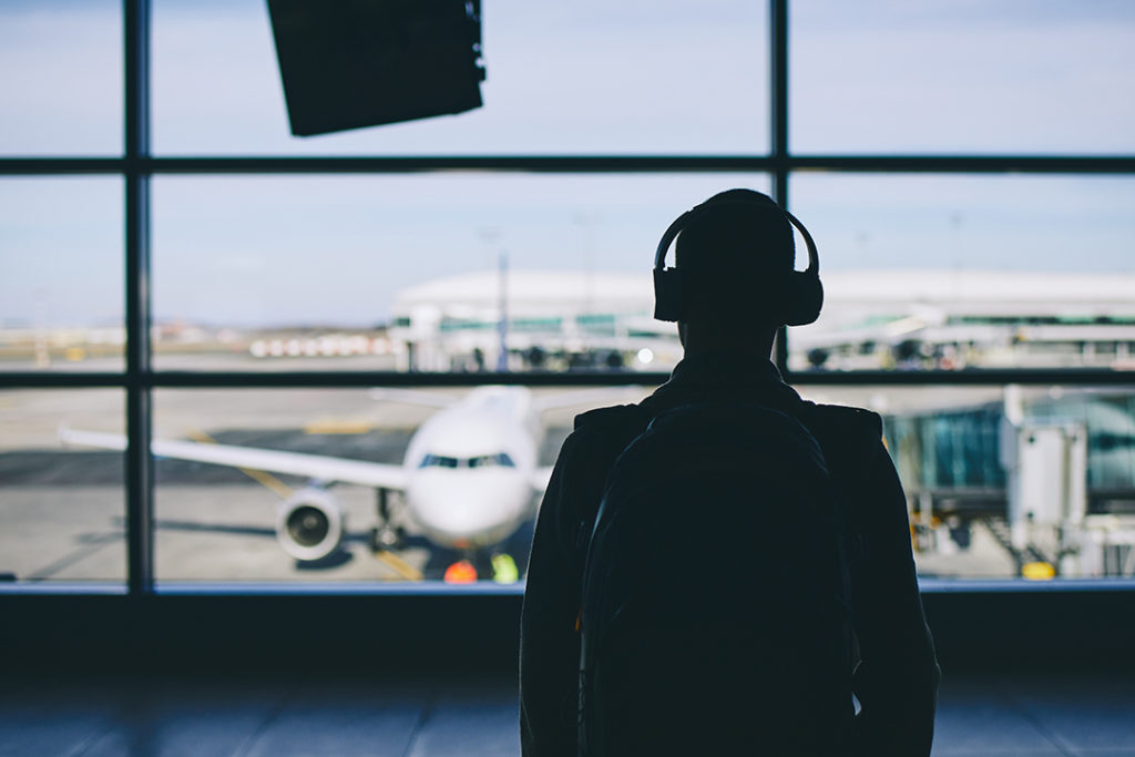 Passenger with headphones. Young man walking through airport terminal to airplane.