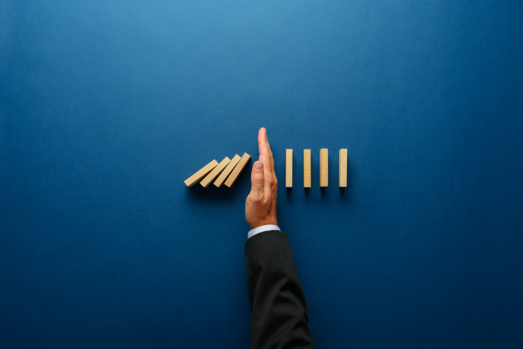 Top view  of businessman hand stopping falling dominos in a business crisis management conceptual image.