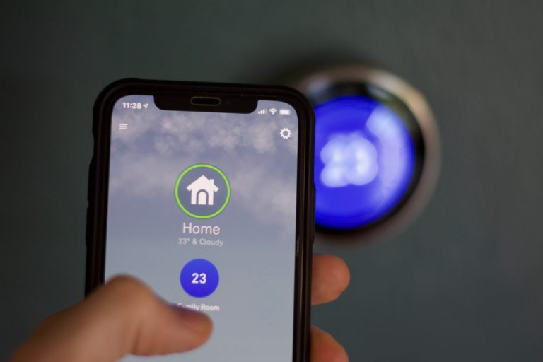 Adjusting temperature of nest thermostat using cell phone app. Cell phone with nest in background