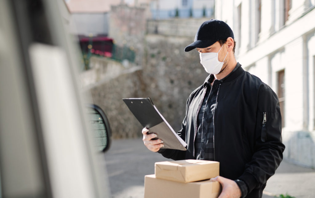 Delivery man courier with face mask delivering parcel box in town, holding clipboard.